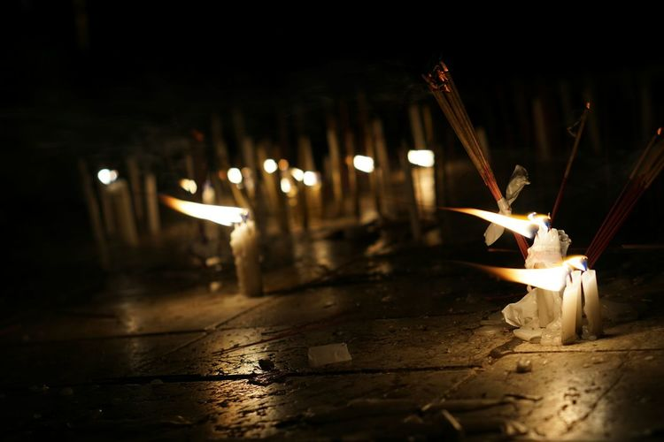 Candles and incense sticks burning on street at night
