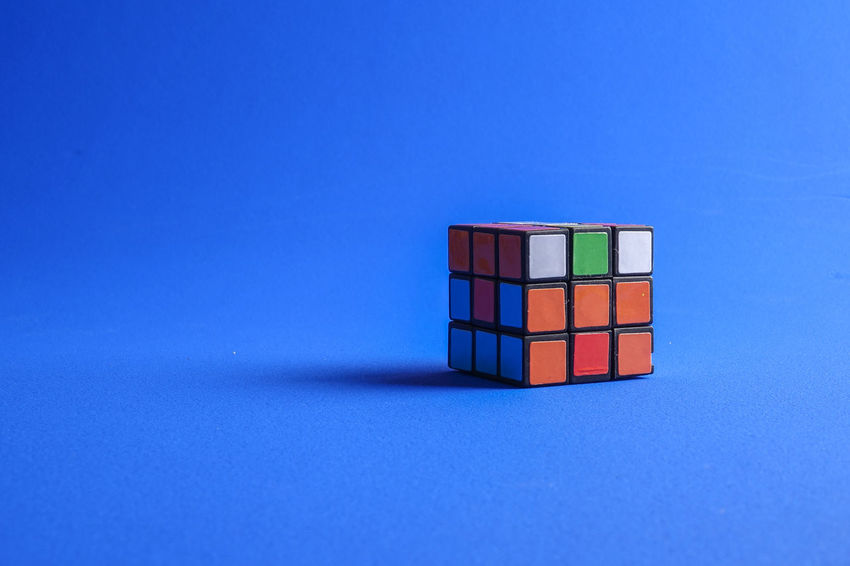 RUBIK'S CUBE , CREATIVITY TOY Creativity Rubik Cube Blue Blue Background Close-up Colored Background Container Copy Space Creativity Cube Shape Indoors  Intelligence Multi Colored No People Orange Color Red Rubik Single Object Still Life Studio Shot Table Toy Toy Block Wood - Material