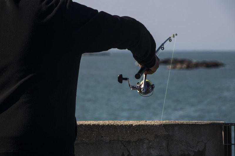 Midsection of man fishing at sea