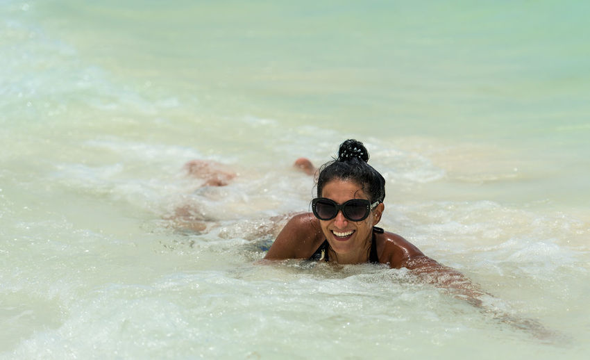 Portrait of smiling woman swimming in sea
