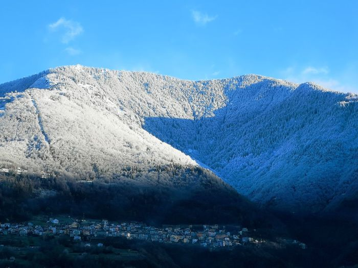 Houses and snowcapped mountains against blue sky