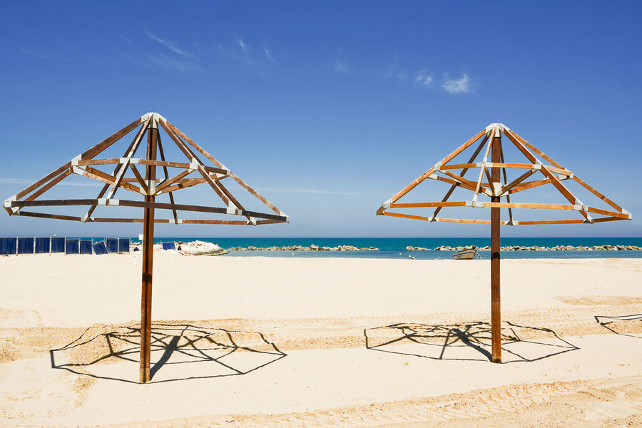Preparations for undiscovered thatched umbrellas Adriatic Adriatico Beach Blue Chieti Coast Francavilla Francavilla Al Mare Francavillaalmare Hut Italy Nature Palm Parasol Preparations Sand Sea Seaside Sky Structure Summer Umbrella Uncovered Water