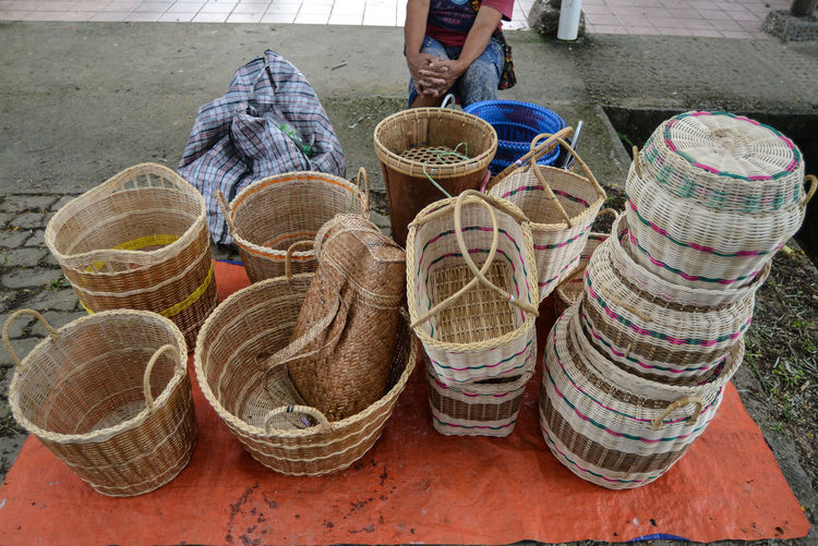 Midsection of woman sitting by baskets for sale at market