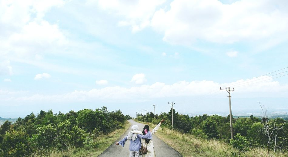 Rear view of friends walking on road against sky