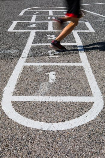 Low section of person playing hopscotch on road