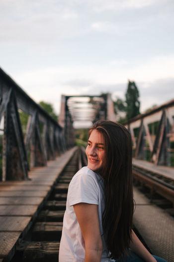Portrait of smiling woman standing on footbridge against sky