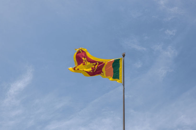 Low Angle View Of Sri Lankan Flag Against Cloudy Sky