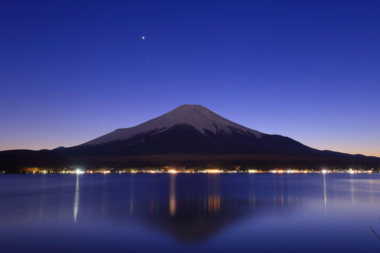 Scenic view of lake by mountains against clear blue sky at night