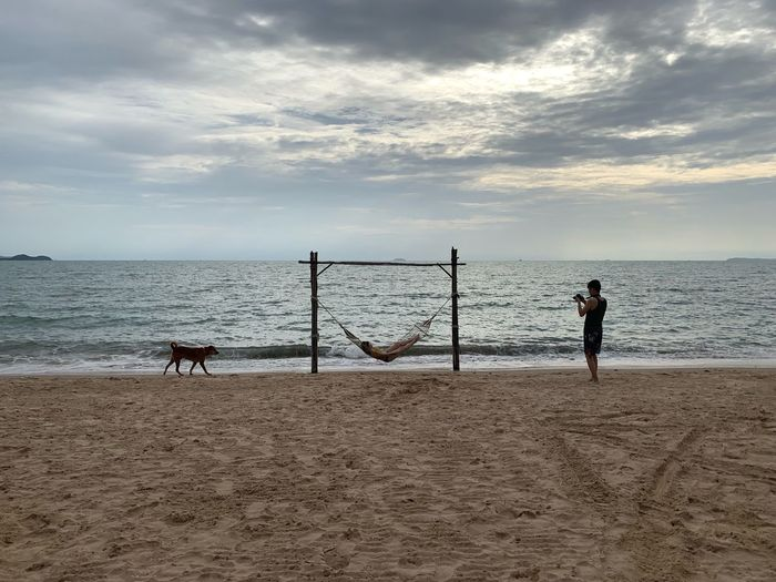 Man photographing woman resting on hammock at beach against sky during sunset