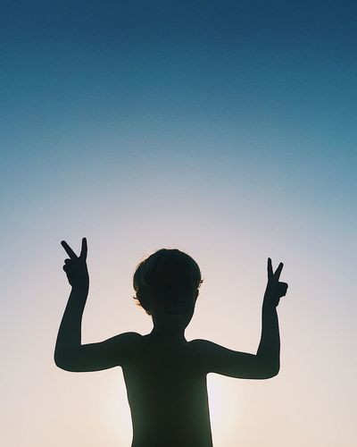 Peace Peace Sign  Silhouette Animal Themes Arms Raised Boys Childhood Clear Sky Day Gesturing Horn Sign Human Hand Leisure Activity Lifestyles Nature One Boy Only One Person Outdoors People Real People Shirtless Showing Silhouette Sky Standing