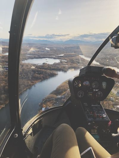 Low section of woman traveling in helicopter over river
