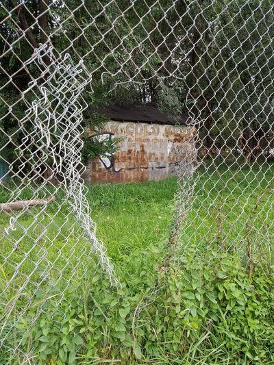 Hole In Fence Showing Old Building