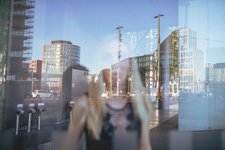 Woman looking through glass window with city reflection