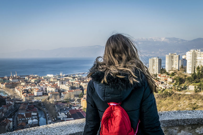 City of Rijeka view from Trsat, Kvarner bay of Croatia. View from above on the city and harbor of Rijeka, Croatia, girl with red backpack in foreground. City Croatia From Behind Mobility In Mega Cities Red Rijeka Architecture Backpack Building Exterior Built Structure Cityscape Clear Sky Day Girl Kvarner Bay Long Hair Nature One Person Outdoors Real People Sea Standing Trsat Warm Clothing Water