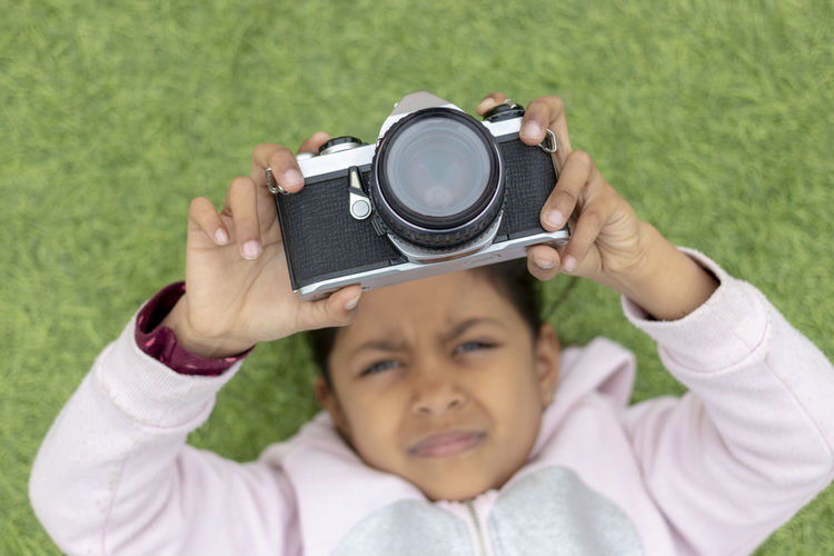 Cute little girl taking pictures with her vintage camera Arms Raised Boys Camera - Photographic Equipment Casual Clothing Child Childhood Close-up Digital Camera Front View Headshot Holding Human Arm Leisure Activity Looking Males  Men Offspring People Photography Themes Portrait Technology