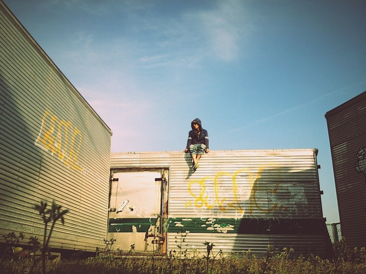 Low angle view of young woman sitting on wall against blue sky