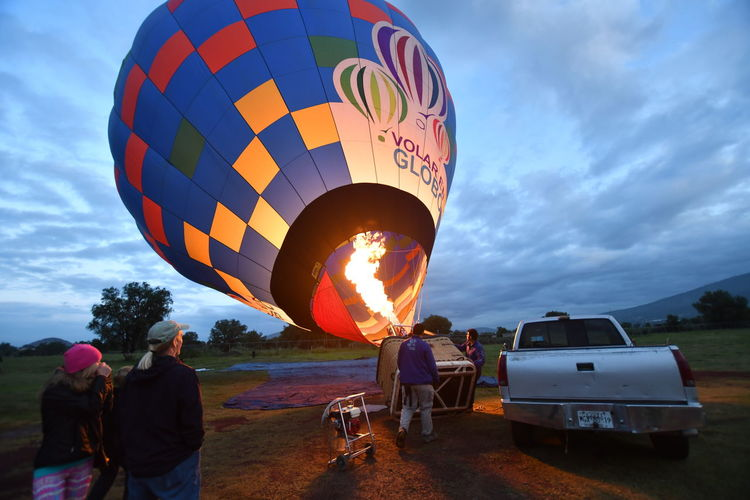 People on hot air balloon against sky