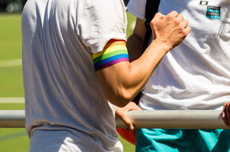 Midsection of man wearing rainbow flag band