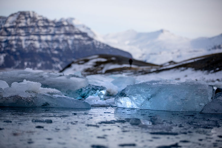 Surface level of frozen lake against mountain during winter