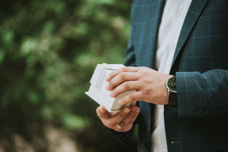 Man in a suit opening a present in a gift box