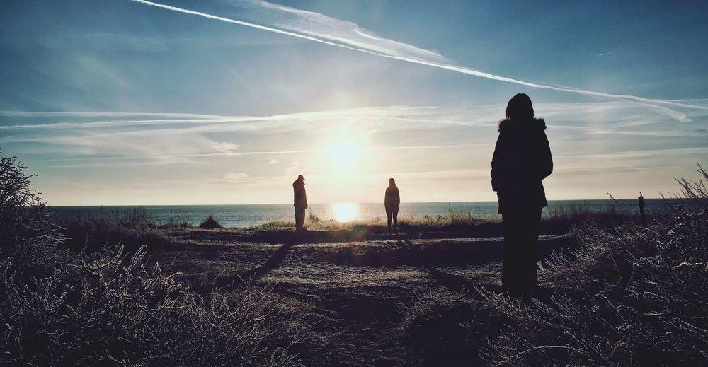 People standing by sea against sky