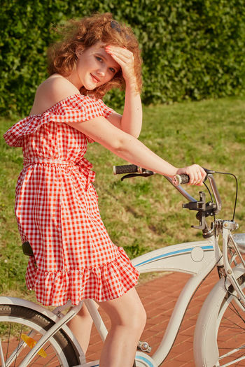 Portrait of a smiling young woman with bicycle