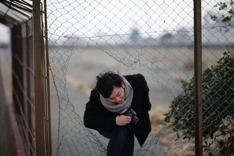 Woman with camera walking in broken fence