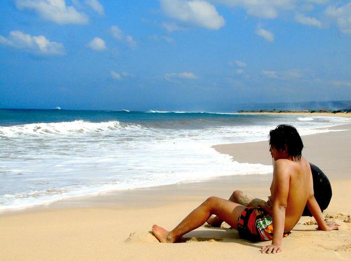 Full length of shirtless man sitting at beach
