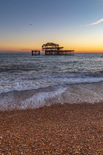 The Pebble Beach and West Pier at Sunset, in Brighton Water Sea Beach Land Sky Sunset Architecture Scenics - Nature Beauty In Nature Horizon Nature Built Structure Horizon Over Water No People Tranquility Wave Tranquil Scene Motion Orange Color Outdoors Pebble Pier West Pier Brighton Architecture