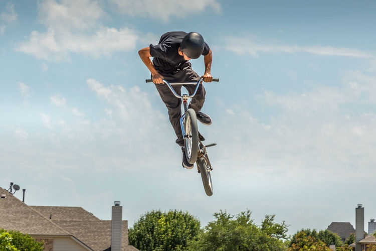 Low Angle View Of Man On Bicycle Jumping Against Sky