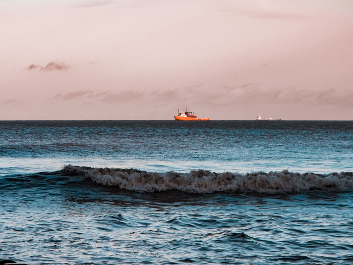 colorful boat Red Boat Orange Color Coral Colored Golden Hour Wave Northsea Two Boats Sea Fishing Boat Water Wave Nautical Vessel Sea Sunset Beach Blue Tide Surf Coastal Feature Surfing Crashing Coastline Seascape Romantic Sky Coast