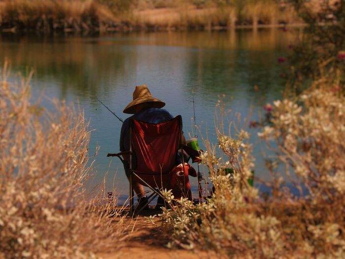 Man fishing Beauty In Nature Casual Clothing Countryside Day Focus On Foreground Forest Holding Lake Leisure Activity Lifestyles Men Nature Non-urban Scene Person Rear View Remote Scenics Selective Focus Tourism Tranquil Scene Tranquility Travel Destinations Water Weekend Activities