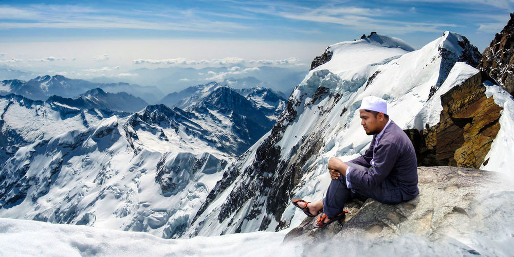 Side view of young man looking away while sitting on snowcapped mountain against sky