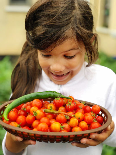 Cute girl holding fruits in plate homegrown tomatoes