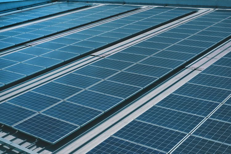 Many photo voltaic solar panels mounted of industrial building roof .