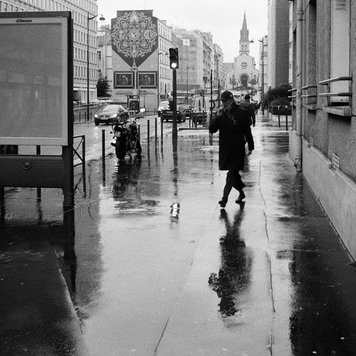Man walking on wet street in city