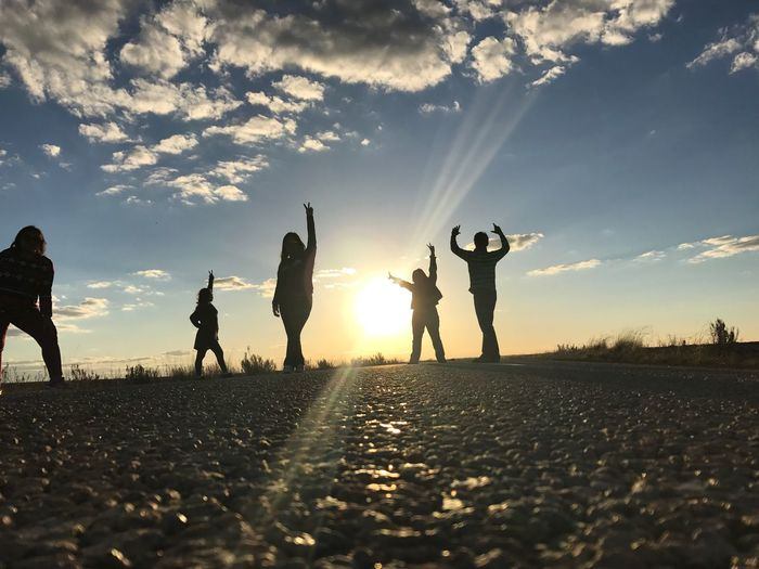 Silhouette friends gesturing on road during sunset