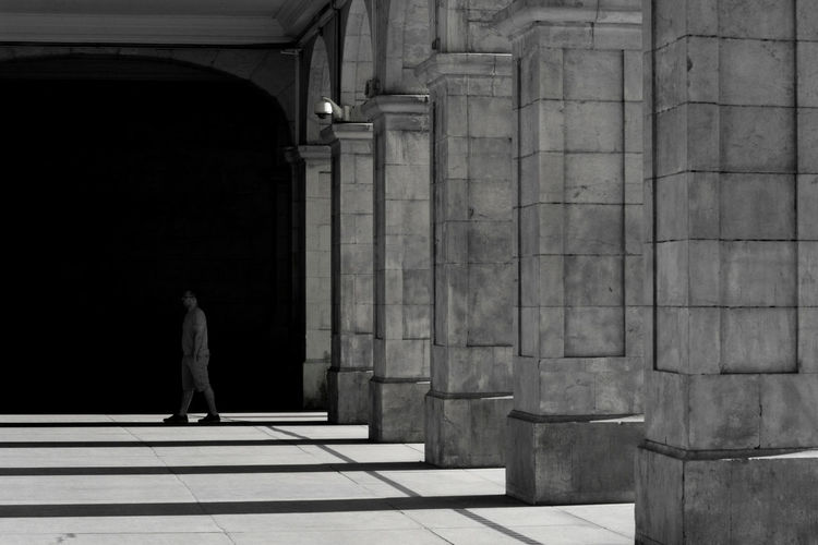 Full length of man walking on corridor by colonnade of historic building