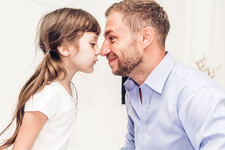 Side view of father and daughter rubbing noses at home