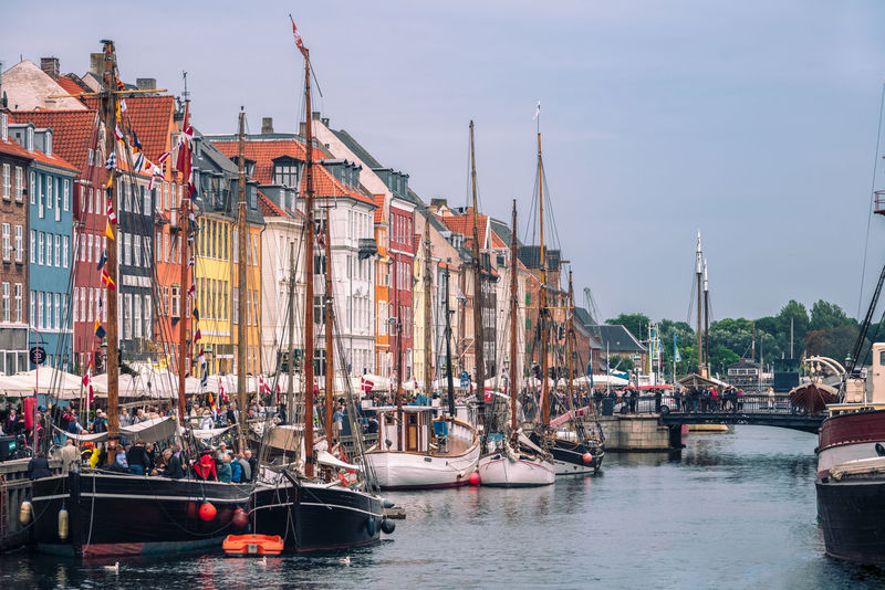 Historical townhouses with wooden sailboats harbored in famous canal Nyhavn, Copenhagen Façade Tourist Attraction  Bridge - Man Made Structure Canal Capital Cities  Colorful Crowd Danish Culture Famous Place Masts Nautical Vessel Sailboat Sky Sun Shades Sunset Townhouses Travel Destinations Water Waterway Wooden Boats
