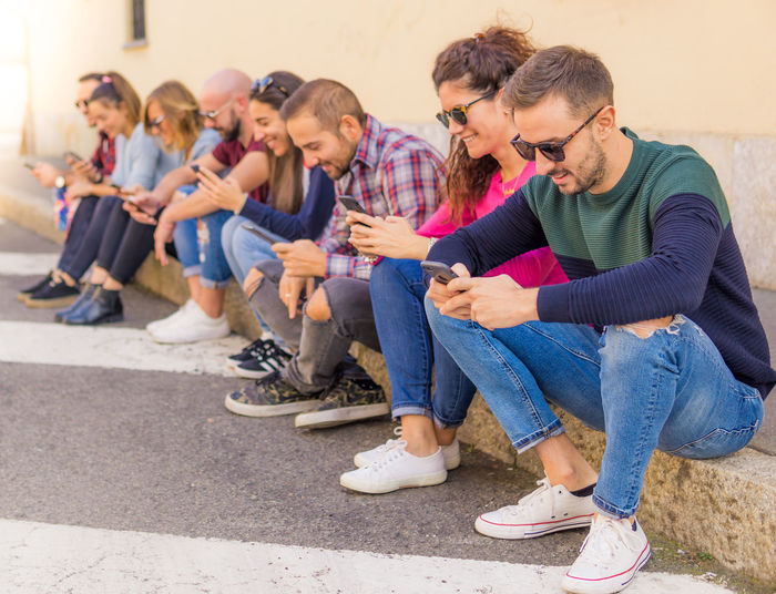 Friends using phones sitting against wall