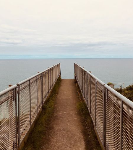 View of wooden bridge over sea against sky
