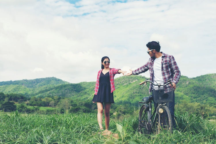 Young couple with bicycle on field against sky
