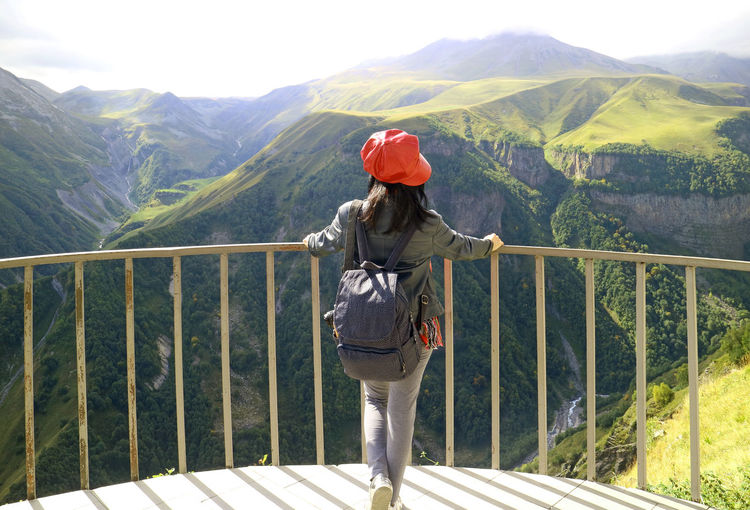 Rear view of woman standing by railing against mountain