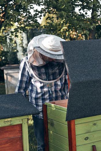 Beekeeper examining honey comb at yard