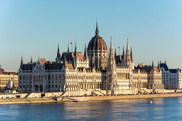 Hungarian Parliament Building By Danube River Against Clear Blue Sky