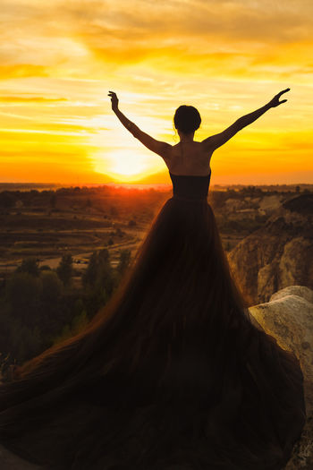 Rear view of silhouette woman standing on land against sky during sunset