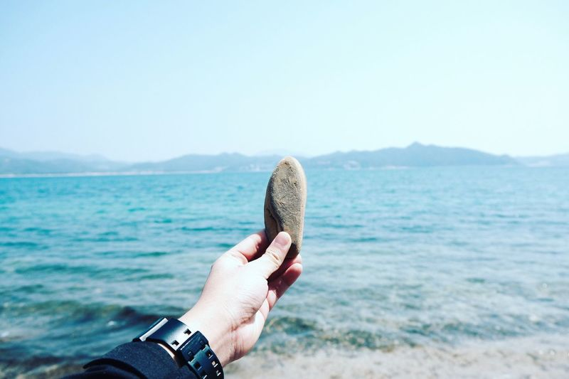Cropped Hand Of Woman Holding Stone Over Sea Against Sky