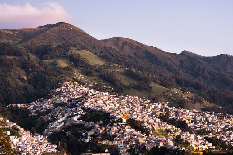Aerial view of buildings and mountains against sky