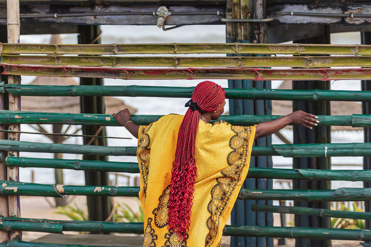 Woman stands behind a bamboo fence on a beach in accra ghana that is forbidden to pass
